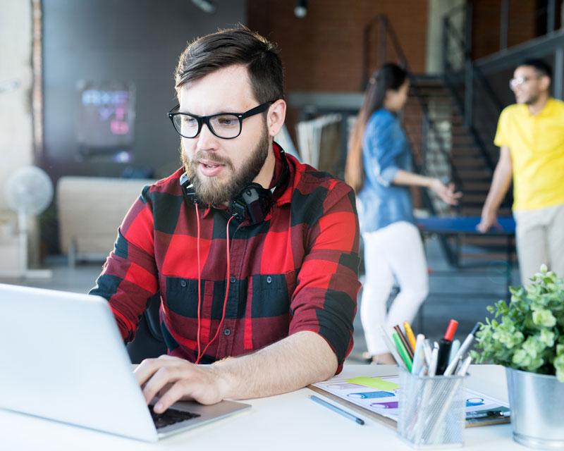 modern-bearded-man-using-laptop-in-coworking-space-XRQLYE3.jpg